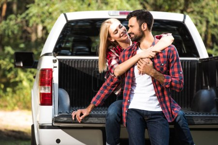 young cheerful couple embracing each other on car trunk outdoors