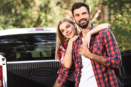 Foto de Enfoque selectivo de la joven pareja abrazándose unos a otros en el baúl del auto al aire libre - Imagen libre de derechos