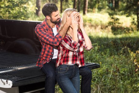 smiling man covering eyes of girlfriend from behind while sitting on car trunk outdoors