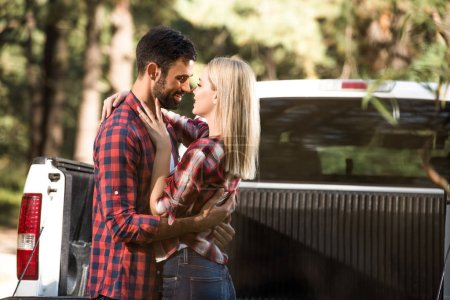 side view of happy young couple looking at each other near pick up car outdoors