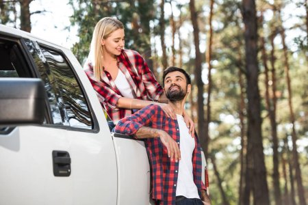 attractive young woman embracing boyfriend while sitting on pick up trunk outdoors