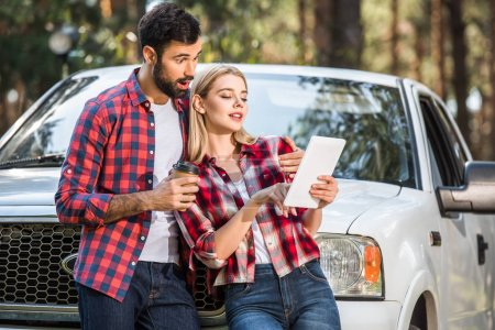 shocked young man with coffee cup standing near girlfriend while she using digital tablet near pick up car outdoors