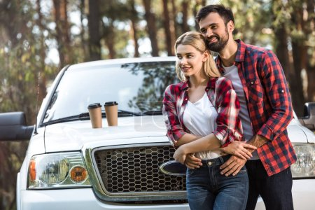 smiling young man embracing girlfriend near pick up car with coffee cups on bonnet outdoors