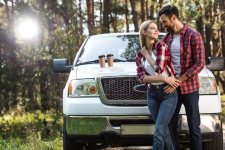 handsome man embracing girlfriend near pick up car with coffee cups on bonnet outdoors