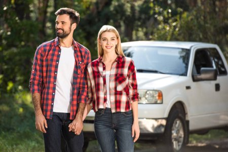 happy young couple holding hands near pick up car in forest