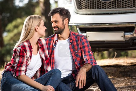 selective focus of happy young couple looking at each other near car outdoors