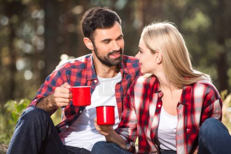 selective focus of couple drinking coffee and talking to each other outdoors