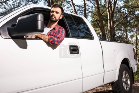 serious young handsome man sitting in pick up car and looking at wing mirror in forest
