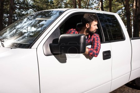 confident young handsome man sitting in pick up car and looking away in forest