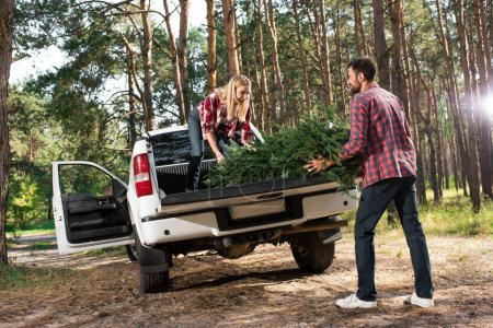 selective focus of young couple loading christmas tree in car trunk in forest