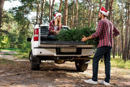 young couple in santa hats loading christmas tree in car trunk in forest