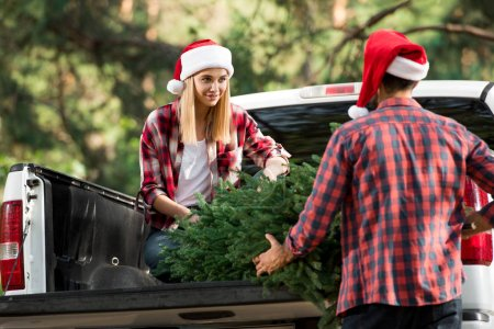 happy young couple in santa hats loading christmas tree in car trunk in forest