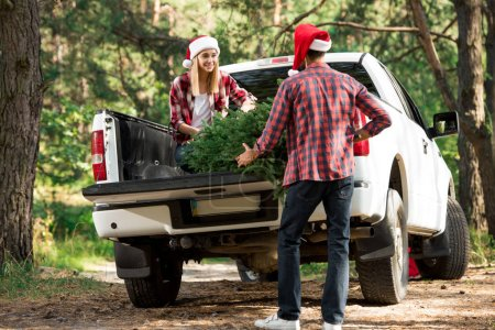rear view of man in santa hat loading christmas tree in car trunk while his girlfriend helping him outdoors