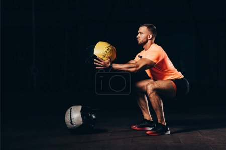 handsome athletic sportsman doing squats with medicine ball in dark gym