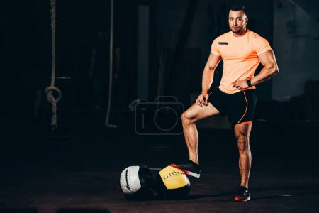 handsome athletic bodybuilder standing in dark gym with medicine balls on floor and looking at camera