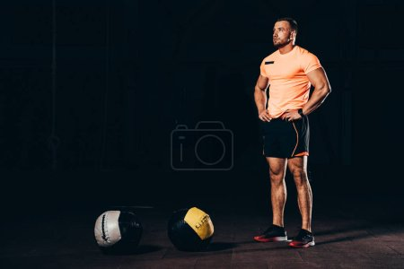 Photo for Handsome athletic bodybuilder standing in dark gym with medicine balls on floor - Royalty Free Image