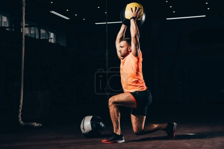 handsome fit sportsman performing lunge with medicine ball overhead in dark gym