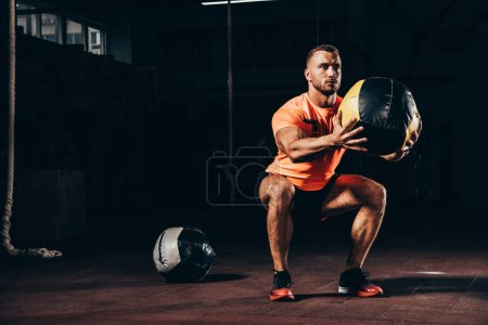 handsome athletic sportsman performing squats with medicine ball in dark gym