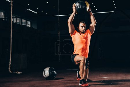 handsome athletic bodybuilder performing lunge with medicine ball overhead in dark gym
