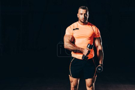 handsome athletic sportsman working out with barbells in dark gym