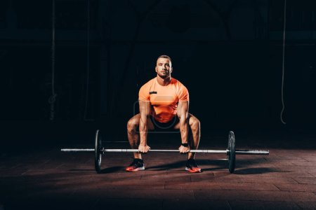 Photo for Handsome athletic bodybuilder lifting barbell in dark gym - Royalty Free Image