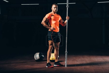 handsome athletic sportsman standing with bar in dark gym and looking at camera