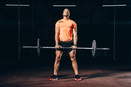 Photo for Handsome athletic man working out with barbell in dark gym and looking up - Royalty Free Image