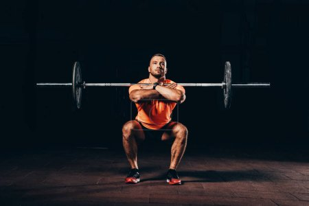 handsome muscular man doing squats with barbell in dark gym