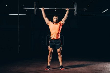 Photo for Handsome muscular man working out with barbell in dark gym - Royalty Free Image