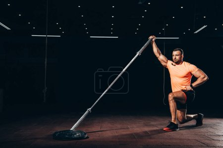 handsome muscular sportsman performing lunge with bar in dark gym