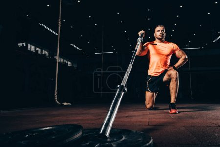 handsome fit man performing lunge with bar in dark gym
