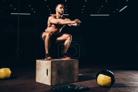 handsome athletic bodybuilder doing squats on cube in dark gym