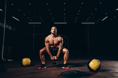 handsome athletic bodybuilder doing squats with kettlebell in dark gym