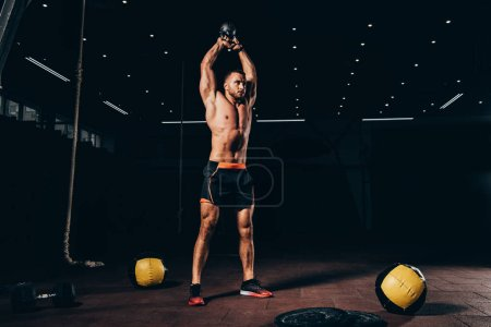 handsome fit sportsman holding kettlebell overhead while working out  in dark gym