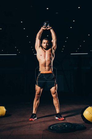 Photo for Handsome muscular man holding kettlebell overhead while working out  in dark gym - Royalty Free Image
