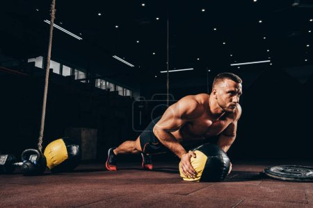 Photo for Handsome athletic sportsman doing push ups on medicine ball in dark gym - Royalty Free Image