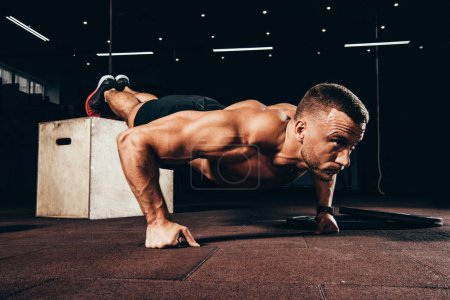 handsome athletic sportsman doing push ups with feet on cube in dark gym