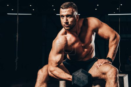 handsome athletic bodybuilder lifting dumbbell while sitting on cube in dark gym
