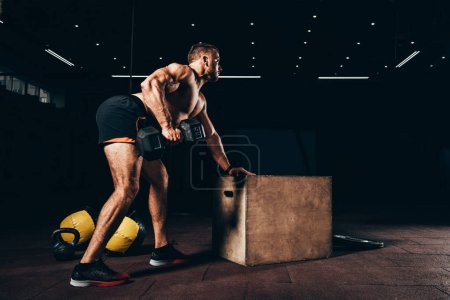 Photo for Handsome athletic sportsman working out with dumbbell in dark gym - Royalty Free Image