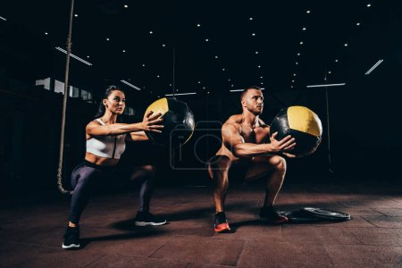 athletic sportsman and sportswoman exercising with medicine balls together in dark gym