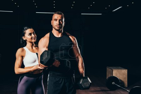 Photo for Athletic bodybuilder exercising with barbell and looking at camera while woman standing behind in dark gym - Royalty Free Image