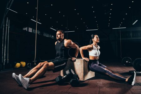 athletic sportsman and sportswoman exercising on cube together in dark gym