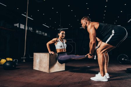 athletic woman exercising with trainer on cube in dark gym