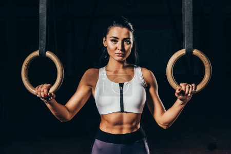 attractive sporty woman with gymnastic rings looking at camera isolated on black