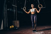 attractive sporty woman working out with gymnastic rings