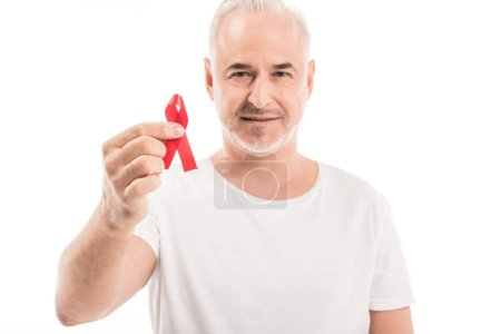 happy mature man in blank white t-shirt holding aids awareness red ribbon and looking at camera isolated on white