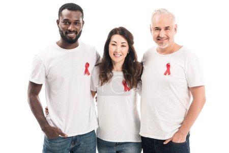 multiethnic group of people in blank white t-shirts with aids awareness red ribbons embracing and looking at camera isolated on white