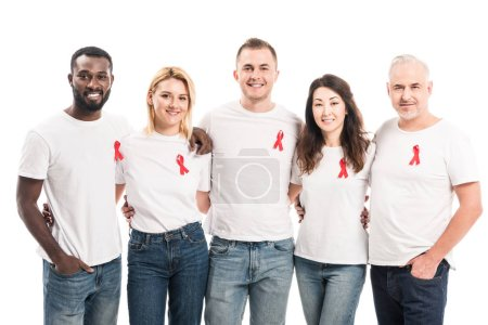 multiethnic group of people in blank white t-shirts with aids awareness red ribbons looking at camera isolated on white
