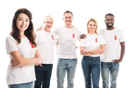 smiling asian woman with crossed arms looking at camera with group of people in blank white t-shirts with aids awareness red ribbons standing isolated on white