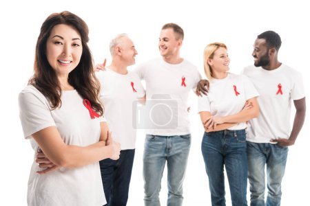 happy asian woman with crossed arms looking at camera with group of people in blank white t-shirts with aids awareness red ribbons standing isolated on white